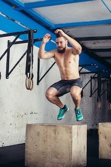 Fit mann macht box jumps in einem fitnessstudio
