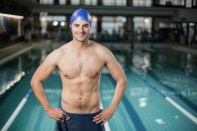 Fit mann mit den händen auf den hüften am pool