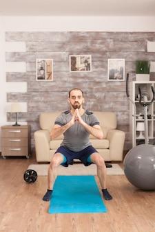Fit mann trainiert seine beine auf yogamatte während der globalen pandemie.