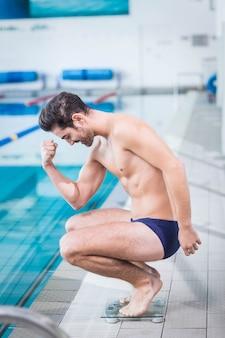 Fit mann triumphiert auf der waage am pool