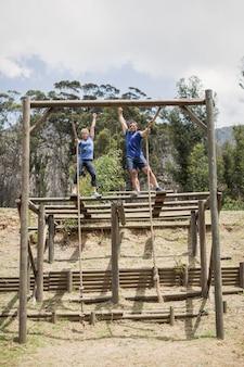 Fit mann und frau klettern das seil während des hindernislaufs im bootcamp hinunter