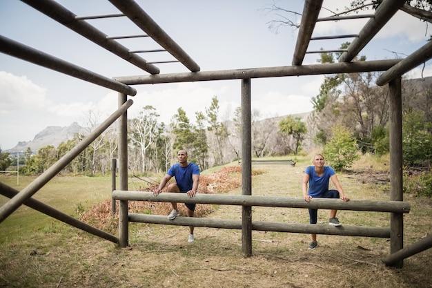 Fit mann und frau klettern kletterstangen während hindernislauf im boot camp