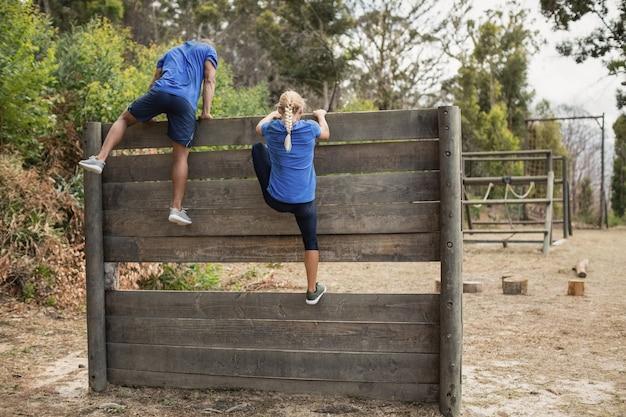 Fit mann und frau klettern über holzwand während hindernislauf im bootcamp