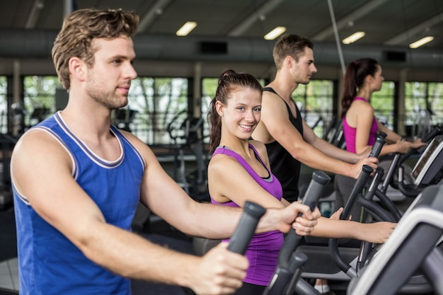 Fit menschen auf ellipsentrainer im fitnessstudio