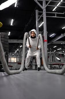 Fit muslimische frau im sportlichen hijab, der crossfit-übungen mit seil im modernen fitnessstudio macht, arabisches frauentraining allein, im sport engagiert