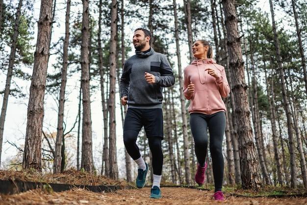 Fit paar, das im herbst durch wälder läuft und sich auf den marathon vorbereitet