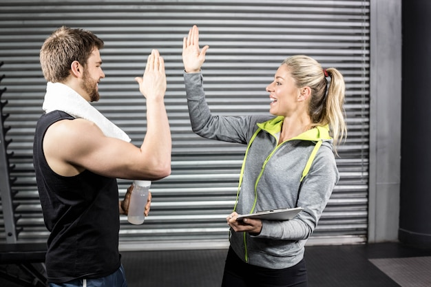 Fit paar high fiving im fitnessstudio