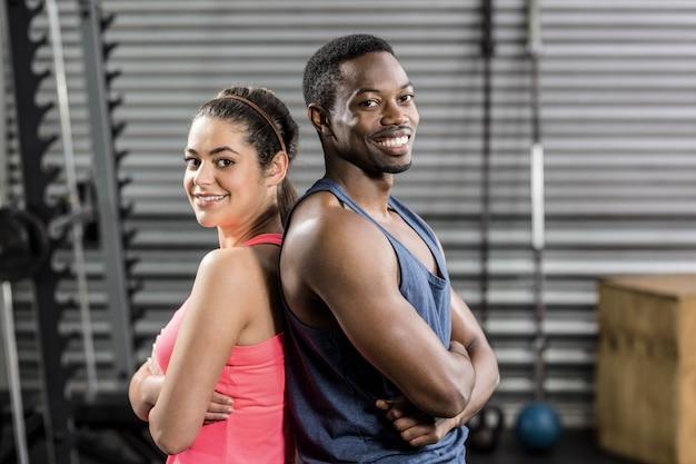 Fit paar rücken an rücken im fitnessstudio