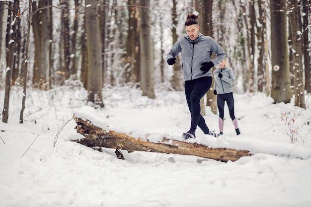 Fit paarrennen im wald am verschneiten wintertag. beziehung, gesunder lebensstil, erfolg