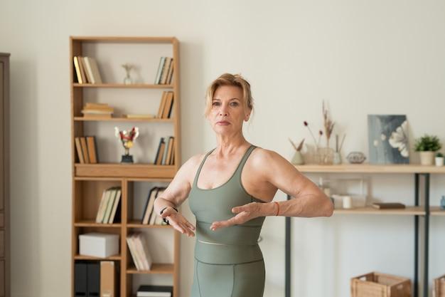 Fit reife blonde frau in grauem trainingsanzug im wohnzimmer stehend mit ihren armen in ellbogen vor sich gebeugt und in ruhe trainieren