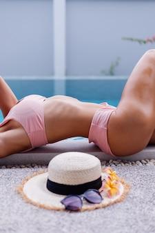 Fit schlanke frau im bikini am rande des schwimmbades genießen urlaub
