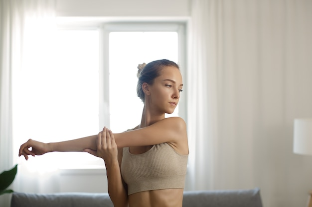 Fit sportfrau, die zu hause trainiert und trainiert