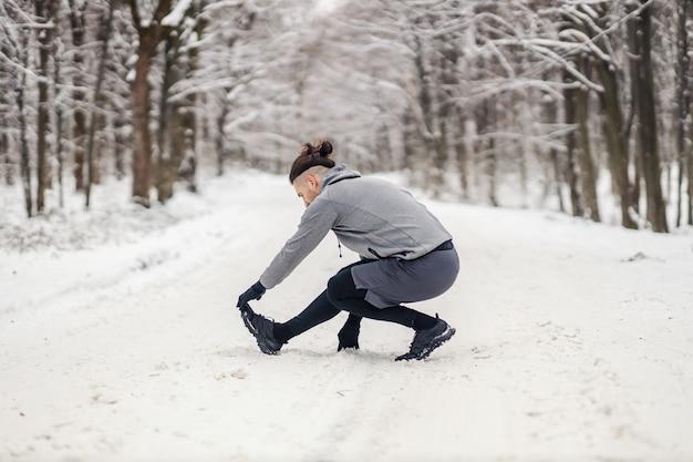 Fit sportler, der aufwärmübungen am verschneiten wintertag im wald macht. winter fitness, gesundes leben