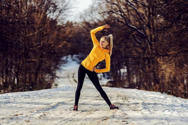 Fit sportlerin, die auf schneebedecktem weg in der natur steht und aufwärmübungen am sonnigen wintertag macht. winter fitness, gesunder lebensstil