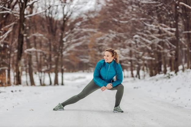 Fit sportlerin, die aufwärmübungen in der natur auf einem schnee macht. schneetag, winterfitness, sport, übungen auf schnee