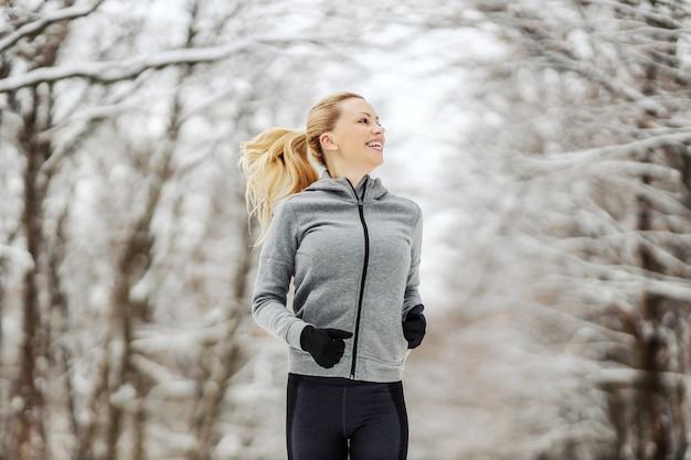 Fit sportlerin, die in der natur am verschneiten wintertag läuft. fitness im freien, gesunder lebensstil, kühles wetter
