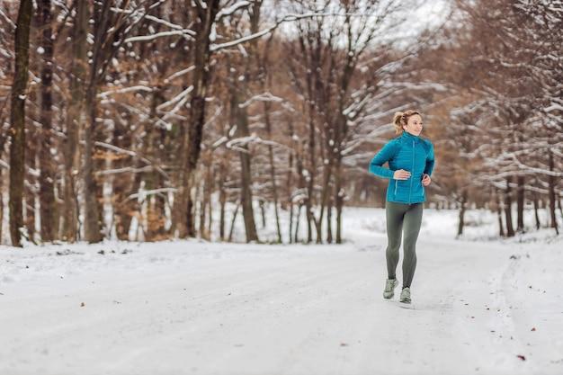 Fit sportlerin, die in der natur auf einem schneebedeckten weg läuft. kaltes wetter, schnee, gesundes leben, fitness