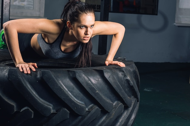 Fit sportliche frau, die liegestütze auf reifenkraft-krafttrainingskonzept tut