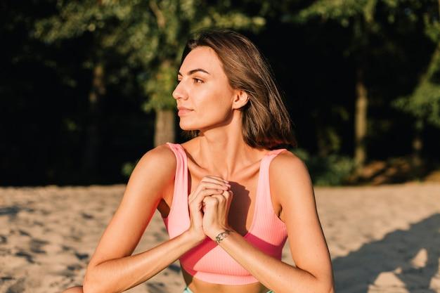 Fit sportliche frau in perfekter form bei sonnenuntergang am strand in yoga-pose ruhig