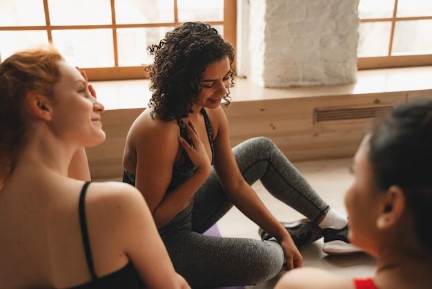 Fit sportliche frauen entspannen nach dem training. intensives fitnesstraining im industriellen loft-fitnessstudio.