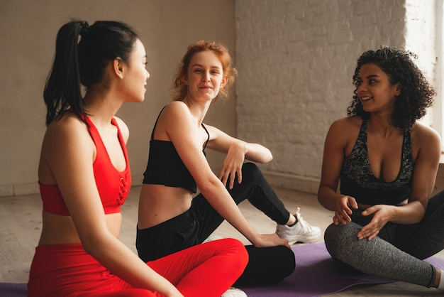 Fit sportliche frauen entspannen und sprechen nach dem training. intensives fitnesstraining im industriellen loft-fitnessstudio.