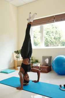 Fit starke junge frau, die zu hause kopfstand auf yogamatte übt