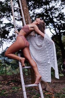 Fit stilvolle gebräunte frau im bikini und weißen strickmantel steht auf tragbaren treppen im wald