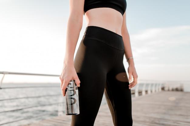 Fit teenager trinkwasser während des trainings am strand