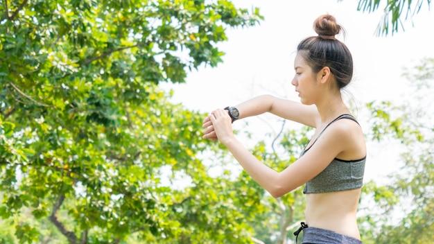 Fit und fest schlank teen lady blick auf die smartwatch gps einstellen