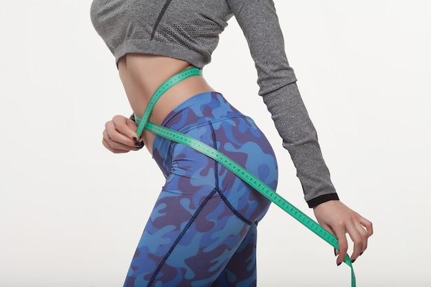 Fit und gesund junge dame misst ihre taille mit einem maßband in zentimetern und millimetern