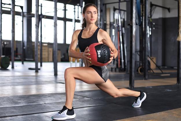 Fit und muskulöse frau, die mit medizinball im fitnessstudio trainiert.