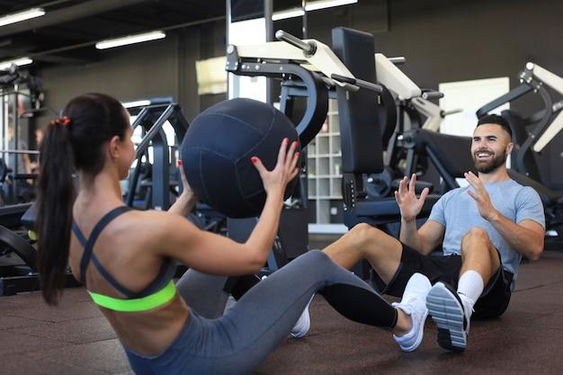 Fit und muskulöses paar, das mit medizinball im fitnessstudio trainiert.