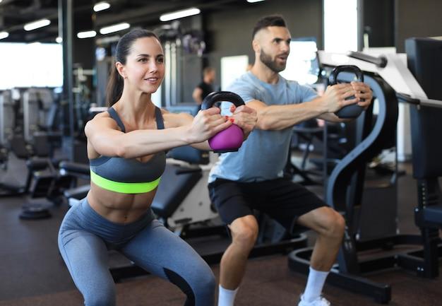 Fit und muskulöses paar konzentrierte sich auf das heben einer hantel während eines trainingskurses in einem fitnessstudio.
