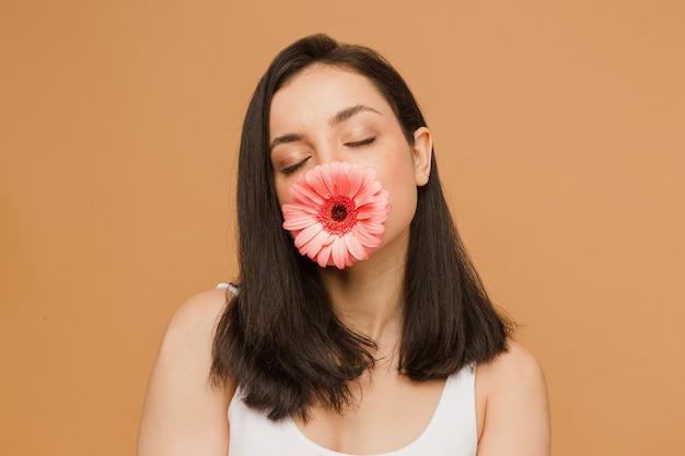 Fit und sportliche frau in unterwäsche. schöne und gesunde frau bedeckt den mund mit blume über beigefarbenem hintergrund. sport, fitness, ernährung, gewichtsverlust und gesundheitskonzept.