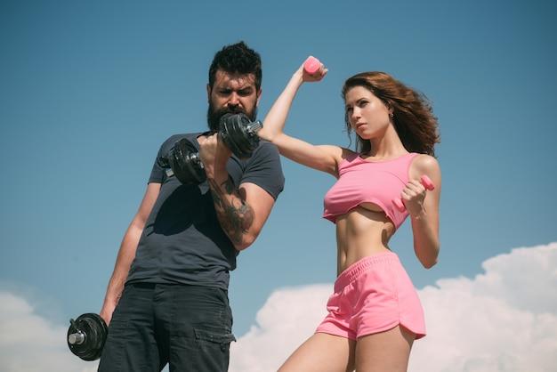Fit und stark. sinnlich fit frau und bärtiger mann, die sportübungen machen. sportliche frau und starker hipster, die körper mit hanteltraining fit halten. sexy paar athleten fühlen sich fit und gesund.