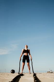 Fit und straffe sportlerin, die im funktionellen fitnessstudio am strand trainiert