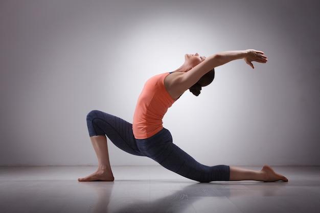 Fit yogini frau praktiziert yoga asana anjaneyasana