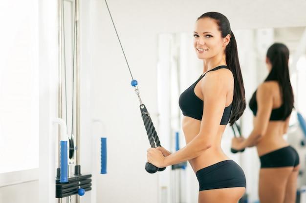 Fites mädchen, das im fitnessstudio trainiert.
