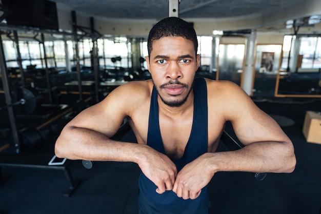 Fitness-afro-amerikaner, der sich nach dem training im fitnessstudio ausruht und in die kamera schaut