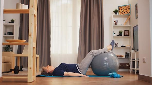 Fitness-ball der älteren frau, der auf yogamatte im wohnzimmer liegt. gesunder lebensstil rentner des alten menschen, der zu hause sport- und wellnesstraining zuhause lebt
