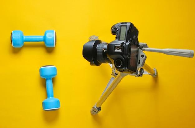 Fitness-blogger. sportkonzept. plastikhanteln und eine kamera auf einem stativ auf einem gelben tisch. draufsicht