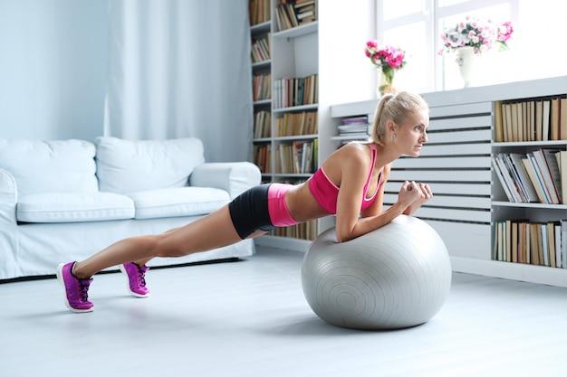 Fitness blonde frau, die strecken mit ihrem übungsball zu hause tut