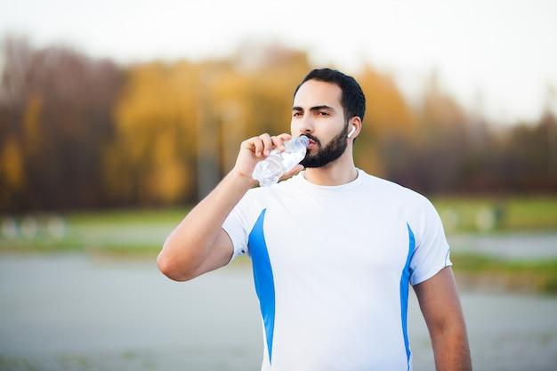 Fitness. erschöpfter läufermann, der auf dem park nach training stillsteht