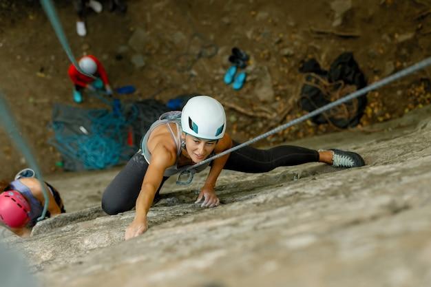 Fitness, extremsport und gesundes lifestyle-konzept - kletterer überwindet anspruchsvolle kletterroute. ein mädchen klettert auf einen felsen. frau im extremsport tätig. extremes hobby.