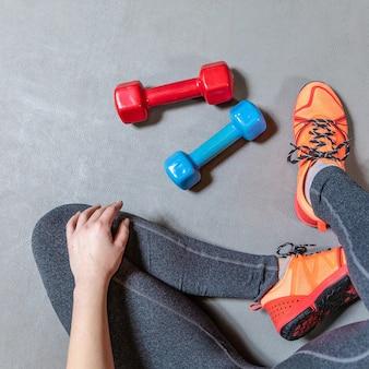 Fitness frau beine mit bunten hanteln draufsicht