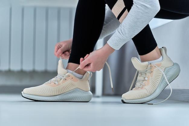 Fitness-frau bindet schnürsenkel an turnschuhen und macht sich bereit für laufen und training. sport treiben und fit sein. sportler mit gesundem sportlichem lebensstil