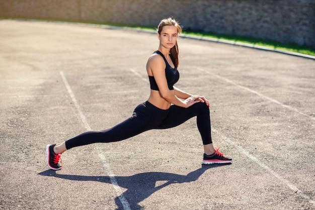 Fitness-frau, die aufwärmroutine auf dem sadium vor dem training tut und körpermuskeln streckt
