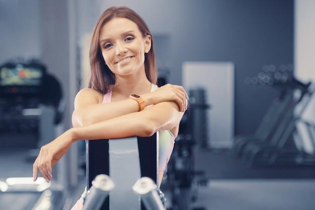Fitness-frau, die beim training im fitnessstudio muskeln aufpumpt hübsches kaukasisches fitness-mädchen