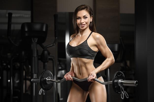 Fitness-frau, die muskeltraining im fitnessstudio aufpumpt