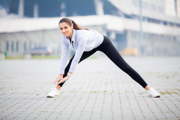 Fitness. frau, die trainingsübung auf straße tut